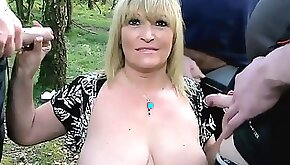 Juicy milf takes out her big boobs and blowjobs three dicks outdoors